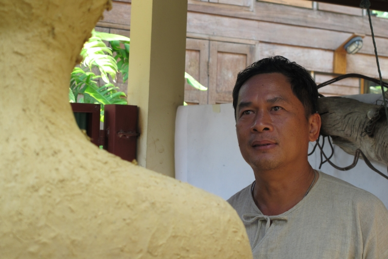 Ajahn Decha, Bamboo Master Builder of Chiangmai Life Construction looking at Buddha