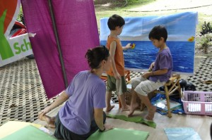 Panyaden School teacher painting with children at Yoga Mala