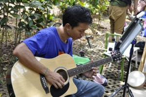Panyaden School teacher playing guitar at Yoga Mala children's booth