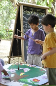 Boys playing fishing game at Panyaden School's children's booth