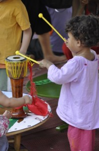 Child playing drums at Panyaden School's booth, Yoga Mala