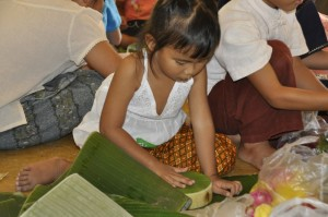 Student of bilingual school in Chiang Mai, Panyaden, placing banana leave on kratong base