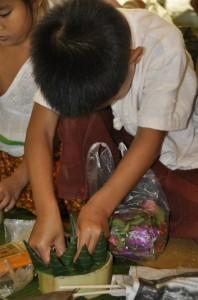 Panyaden schoolboy decorating krathong base with banana leaves