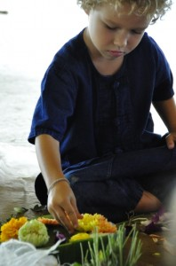 Nursery student adding flowers to his krathong at Panyaden School, bilingual school in Chiang Mai