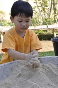Nursery student making EM balls at Panyaden School