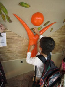 Panyaden School student pinning a leaf to the paper tree after having finished reading a book