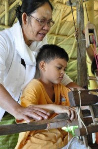 Panyaden School student learning to weave cotton
