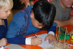 Student writing down in Thai & English what he has learnt about bugs at Science fair, Panyaden School