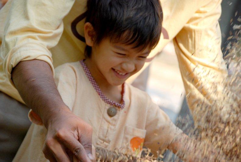 Panyaden School kindergarten student laughing as he learns to thresh rice
