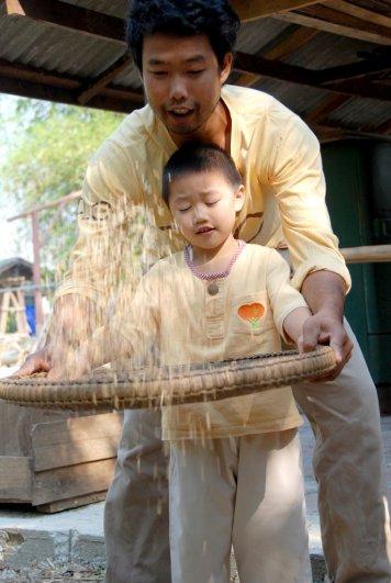 Student of bilingual school, Panyaden, learning to thresh rice