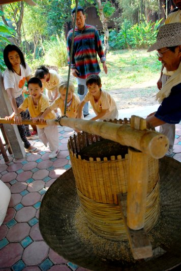 Panyaden School students learning to process rice at a mill