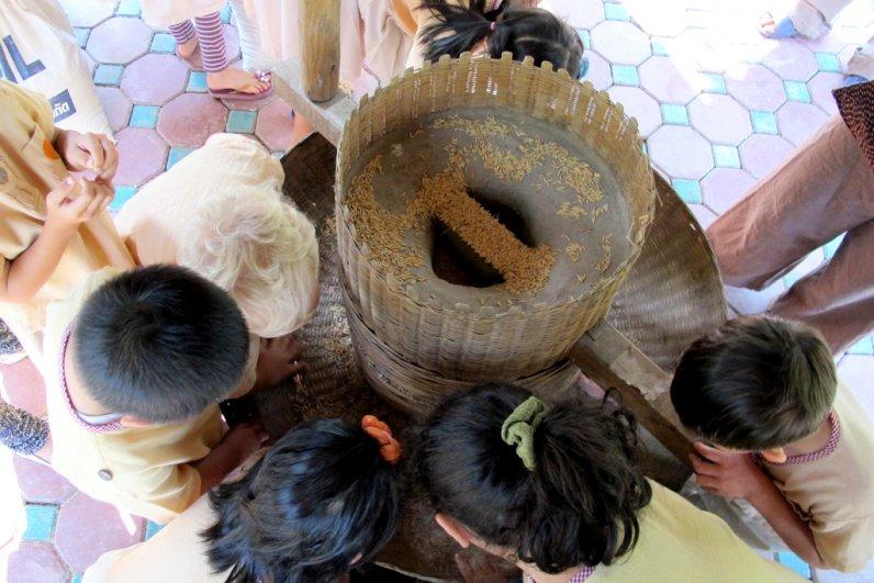 Panyaden School's kindergarten students around a rice miller
