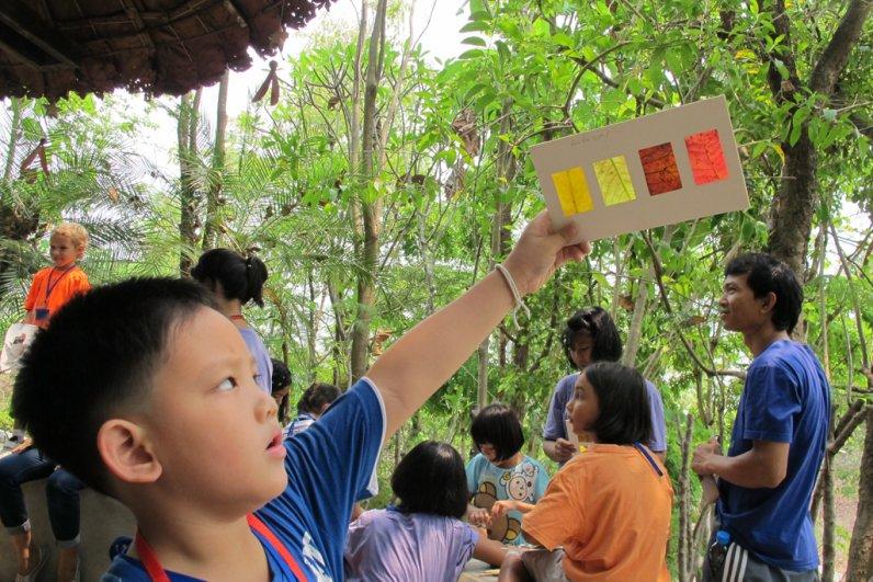 Panyaden School Thai student showing off slides of plants