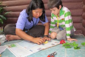Panyaden School teacher working on art piece with Summer School student