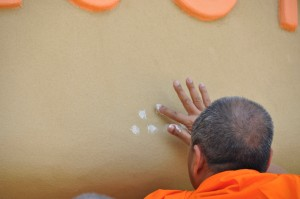 Buddhist monk dotting the Panyaden School sign - blessings for the green bilingual school in Chiang Mai