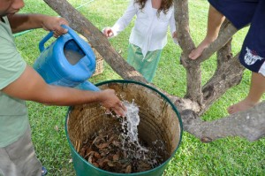 Panyaden School gardener adding liquid mixture to leaves for composting - an eco-friendly practice at Panyaden School