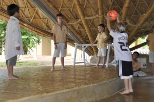 Panyaden School boys acting out football game at their green school's bamboo assembly hall