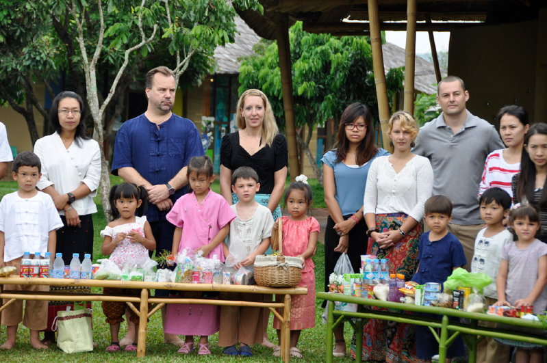 Thai and foreign students & teachers of Panyaden, bilingual school in Chiang Mai, waiting to offer alms