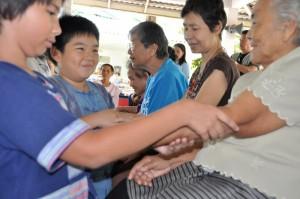 Student giving elder a massage as part of community service project, Panyaden School Chiang Mai