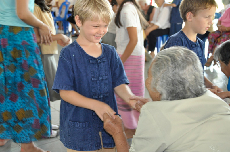 Panyaden School student giving massage to senior citizen, community service by the school in Chiang Mai