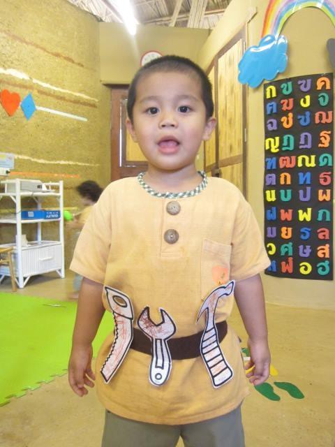 Panyaden nursery student with tool belt he made in class, Panyaden School