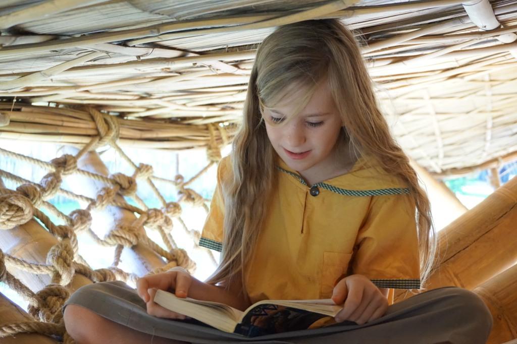Prathom student reading in school assembly hall, Panyaden School