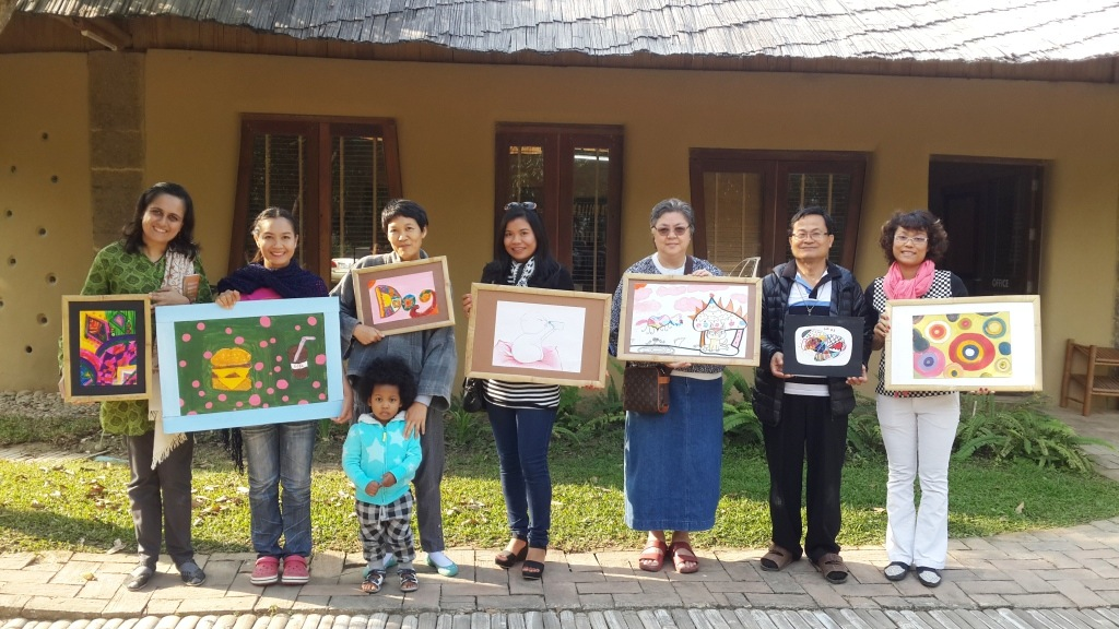 Panyaden parents with their paintings won at the school's silent auction (Giving Week)