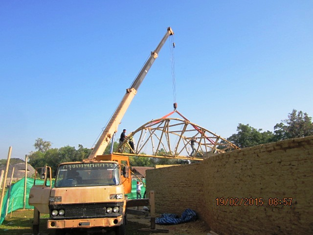 Bamboo roof structure being placed on classroom building by crane, Panyaden School