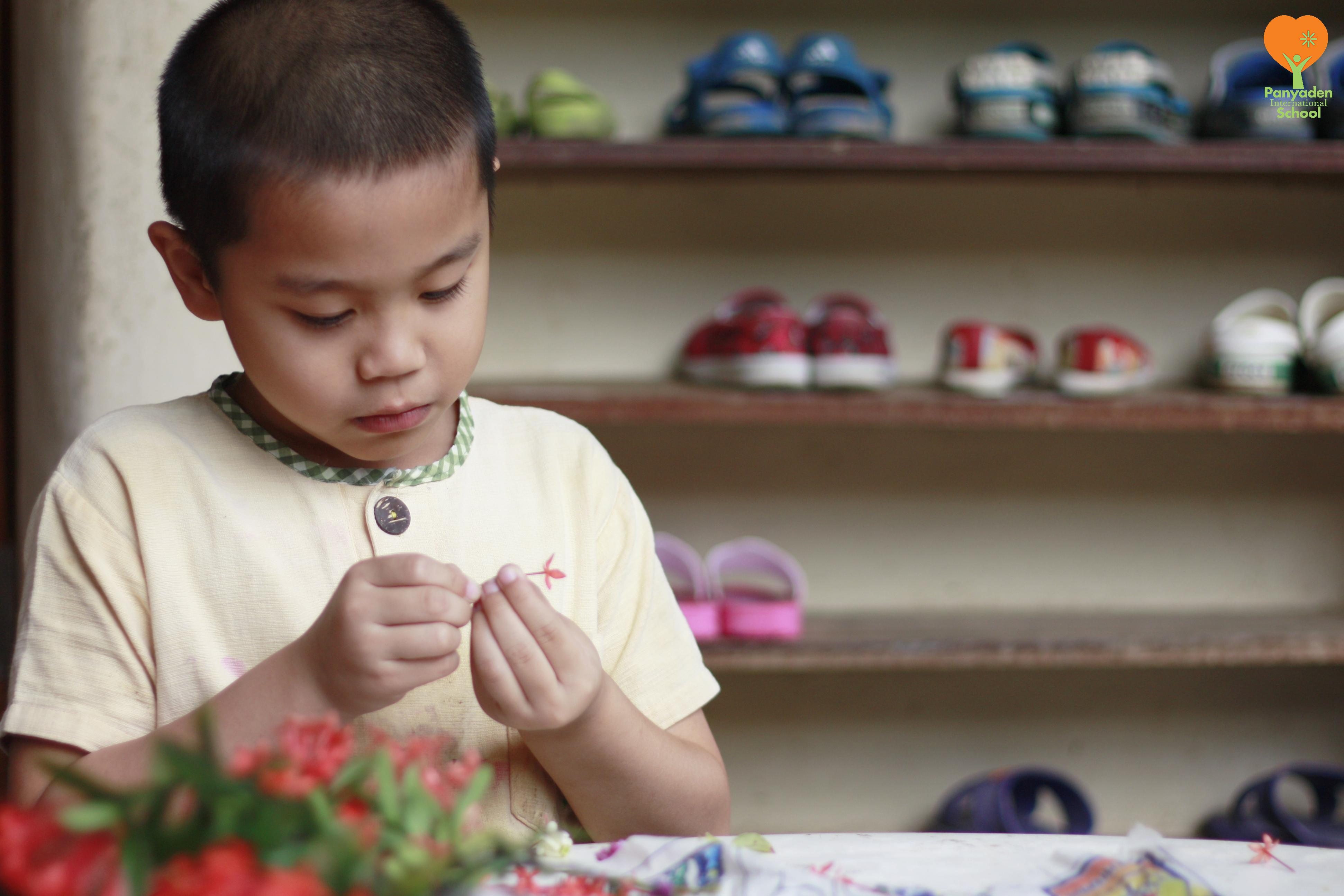 Student stringing flowers for teachers on Wai Kru Day in Thailand, Panyaden International School