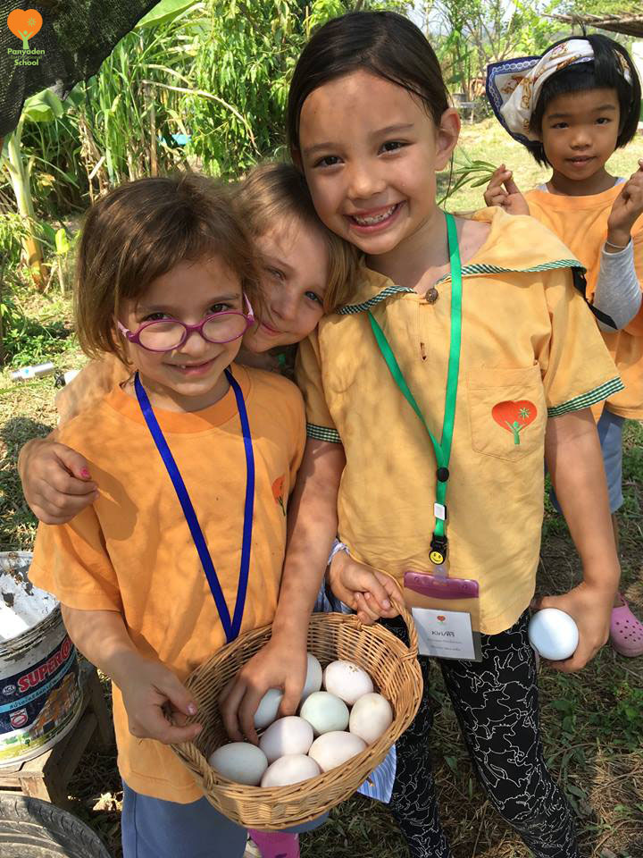 Panyaden International School Chiang Mai students with eggs they gathered during their rice mill visit