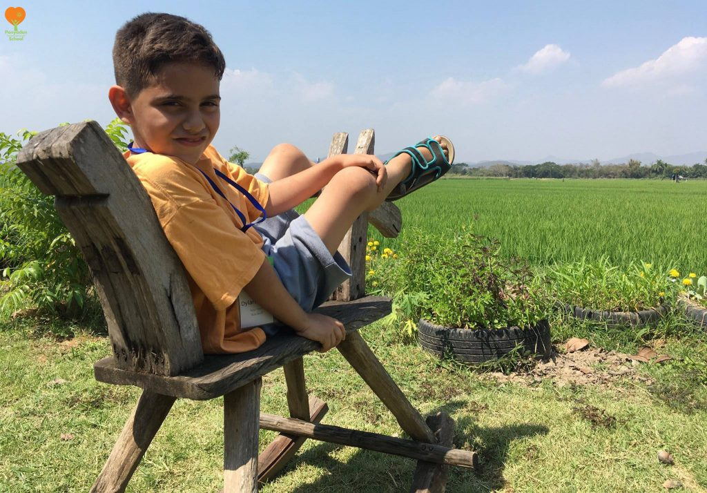 Panyaden International School student enjoy sitting a rocking horse on the field of a rice mill