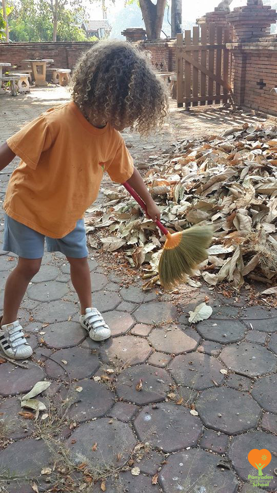 Panyaden K2 social contribution day 2017 - student sweeping leaves