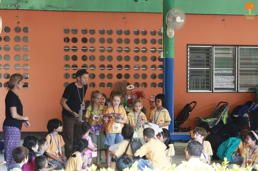 Reading a story aloud, Panyaden primary students at Viengping Children's Home for the school's social contribution day