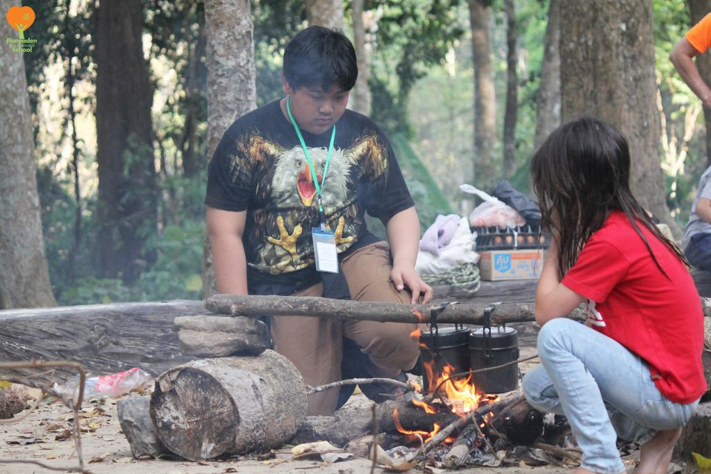 Panyaden International School primary students cooking their dinner at camp