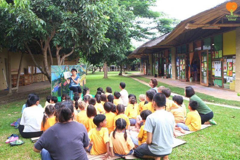 Panyaden parent reading stories to students in school garden