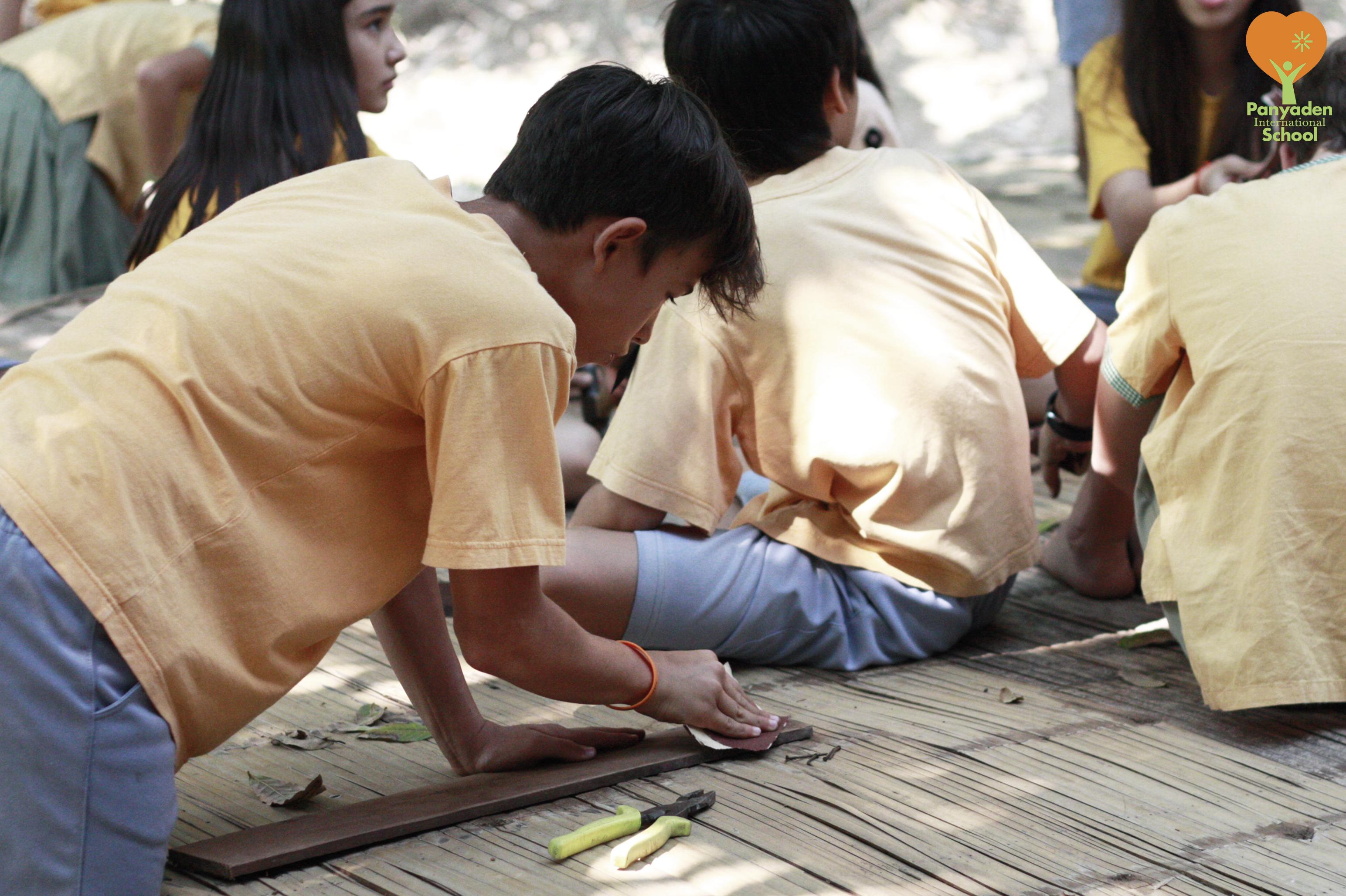 Panyaden Year 6/7 student sanding down wooden signboard for school swimming pool