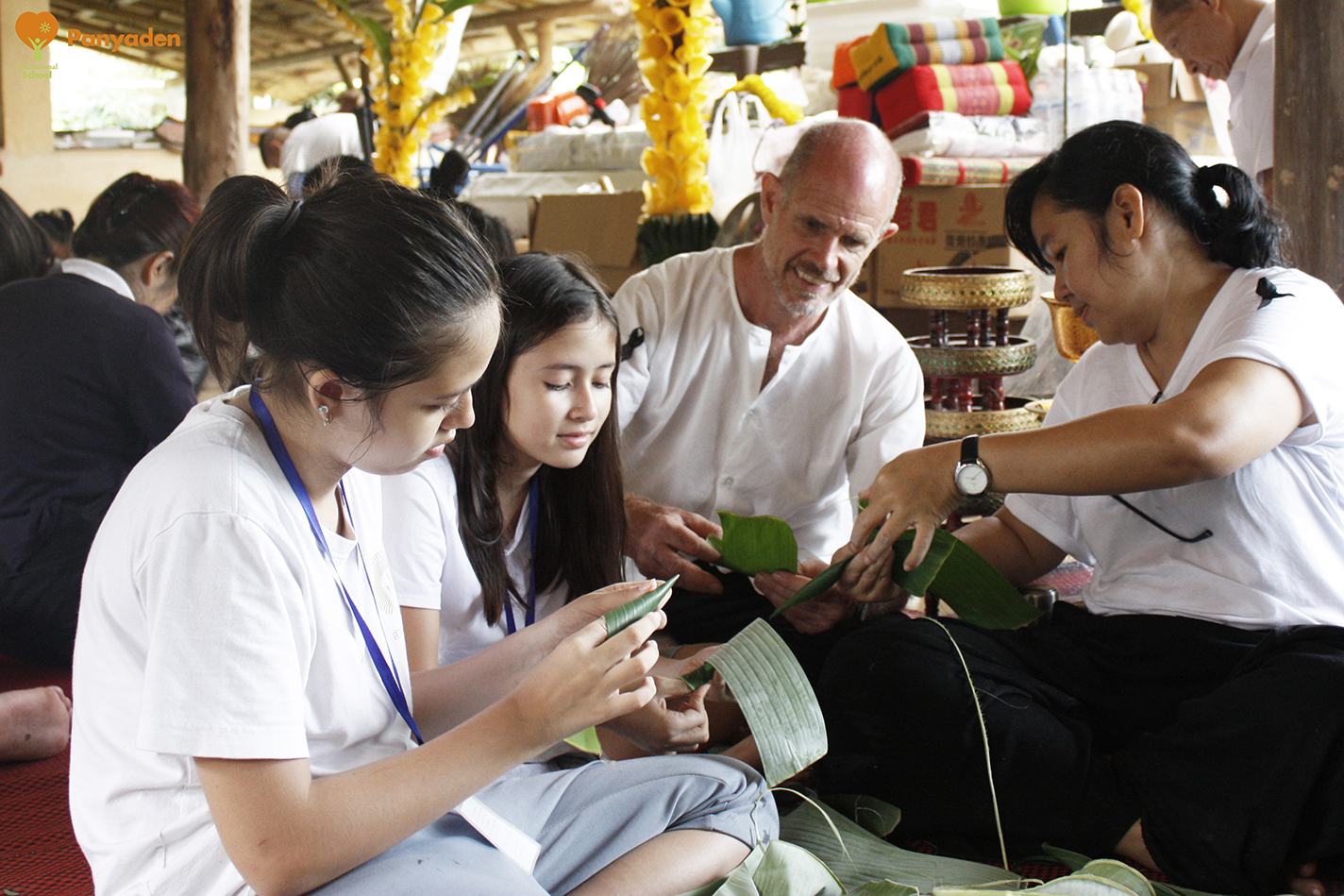 Panyaden students and parents making banana leaf receptables for offerings Jula Khatina in CHiang Rai