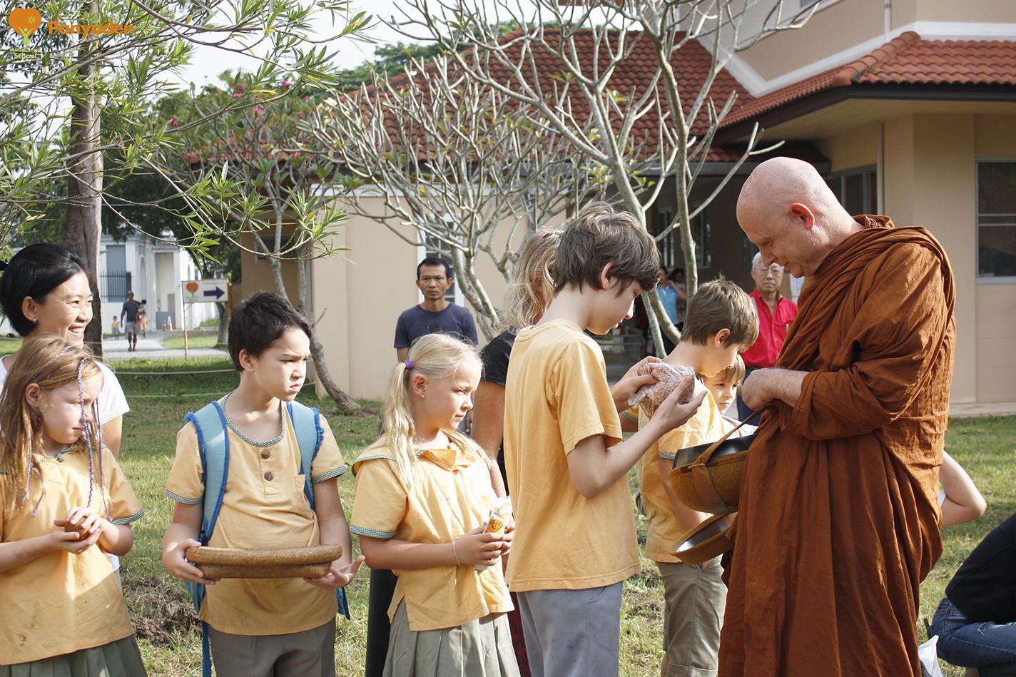 Students offering morning alms to Venerable Ajahn Jayasaro at Panyaden temporary campus